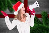 Festive blonde shouting through megaphone against festive bow over wood
