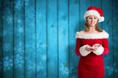Pretty girl in santa outfit against blurred snowflakes on planks