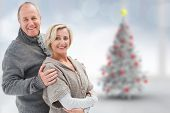 Mature winter couple against blurry christmas tree in room