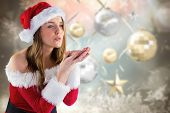 Sexy santa girl blowing over hands against blurred christmas background