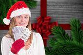 Festive blonde showing fan of dollars against festive bow over wood