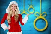 Pretty girl presenting in santa outfit against blurred christmas background