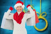 Festive woman holding shopping bags against blurred christmas background