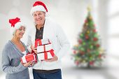 Festive mature couple holding christmas gifts against blurry christmas tree in room