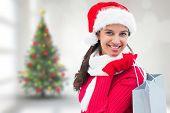Festive brunette holding shopping bag against blurry christmas tree in room