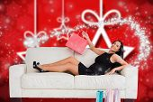 Woman sitting with shopping bags against blurred christmas background