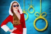Cool santa girl wearing sunglasses against blurred christmas background