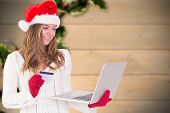 Festive blonde shopping online with laptop against blurred holly on wood