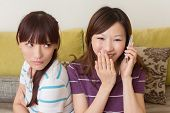 Concept of relationship, one girl talk on phone and another feel unhappy.