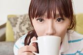 Asian woman drink a cup of coffee, closeup portrait.