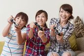 Friendship, technology, games and home concept - smiling female friends playing video games at home.