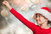 Festive girl hanging decoration against blurred christmas background