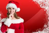 Pretty girl in santa outfit against christmas themed snow flake frame