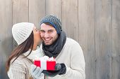 Winter couple holding gift against pale grey wooden planks