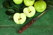 Ripe apples with knife on wooden background