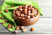 Hazelnuts in wooden bowl, on napkin on wooden background