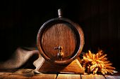 Old barrel with wheat on table on wooden background