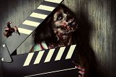 Filming a horror movie. Female zombie holding clapper board. Cinematography. Halloween.