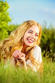 Lovely smiling young woman with magnificent blonde hair in the meadow. Countryside. Summertime.