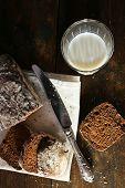 Sliced rye bread, glass of fresh milk and knife on white napkin on wooden background