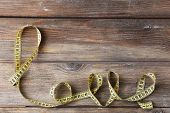 Love word formed with measuring tape on wooden background