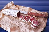 French salami and knife on craft paper on dark blue wooden background