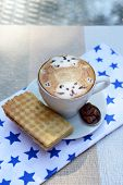 Cup of coffee with cute drawing on table, close up