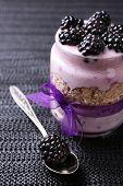 Healthy breakfast - yogurt with  blackberries and muesli served in glass jar, on dark wooden background