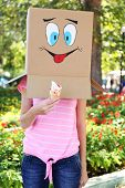 Woman with cardboard box on her head with happy face holding ice cream, outdoors