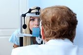 Optometry concept - pretty young woman having her eyes examined by eye doctor