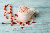 Cranberry milk dessert in glass and glass jar, on color wooden background