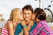 Two beautiful girls kissing smiling one cute boy