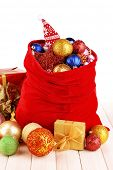 Red bag with Christmas toys on bright background