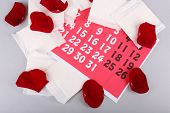Sanitary pads and rose petals on red calendar on light grey background