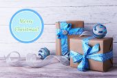 Holiday gift boxes decorated with blue ribbon on table on wooden wall background