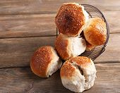 Tasty buns with sesame on color wooden background