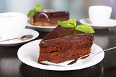 Pieces of chocolate cake on plates and cup of tea on wooden table on natural background
