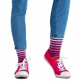 Female legs in colorful socks and sneakers isolated on white