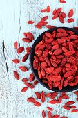 Goji berries in black saucer on blue wooden background