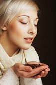 Closeup portrait of pretty blonde girl hold hot roasted coffee beans in hands
