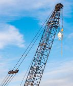 stock photo of boom-truck  - The hoisting crane with pulley and hook in construction site against blue sky background - JPG