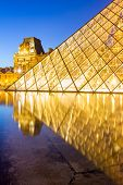 Paris - June 18: Louvre museum at dusk on June 18, 2014 in Paris. This is one of the most popular tourist destinations in France displayed over 60,000 square meters of exhibition space.