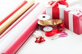 holidays and celebration concept - close up of christmas presents, decoration paper, ribbons and scissors