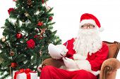 christmas, holidays and people concept - man in costume of santa claus with notepad and pen