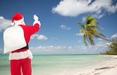 christmas, holidays, travel and people concept - man in costume of santa claus with bag writing something from back over tropical beach background