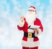christmas, holidays, gesture and people concept - man in costume of santa claus with notepad pointing finger up over blue lights background