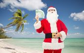 christmas holidays, winning, currency, travel and people concept - man in costume of santa claus with euro money over tropical beach background