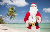 christmas, holidays, travel and people concept - man in costume of santa claus with clock showing twelve pointing finger over tropical beach background