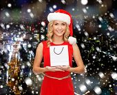 luxury, advertisement, holydays and sale concept - smiling woman in santa helper hat with white blank shopping bag over snowy night city background