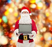christmas, advertisement, technology, and people concept - man in costume of santa claus with laptop computer over red lights background